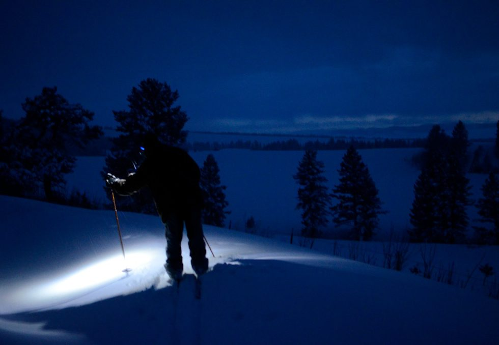 An 11-year old Boy Scout shines his headlamp on a 20-degree night while skiing in the dark late on a Friday night, searching for a remote cabin in the Gallatin National Forest, Crazy Mountains, Montana.